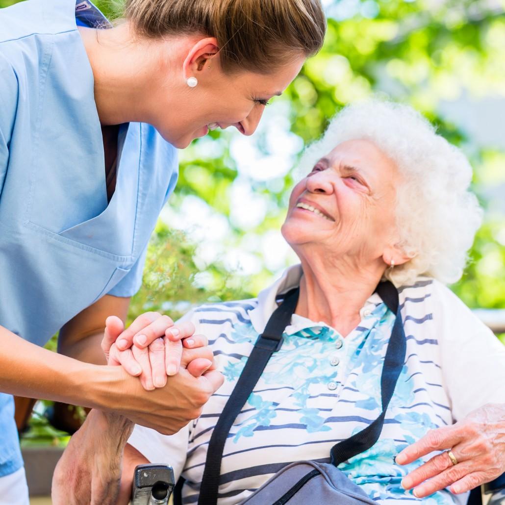 Pflegekraft hält Hand von älterer Dame im Rollstuhl