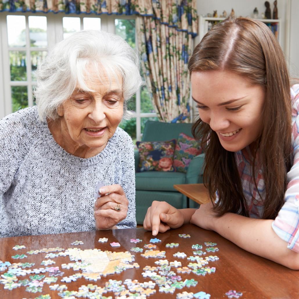 Ältere Dame und jüngere Frau puzzlen